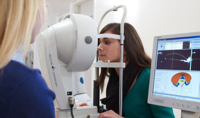 Patientin bei Hornhautuntersuchung mit dem Oculus Pentacam